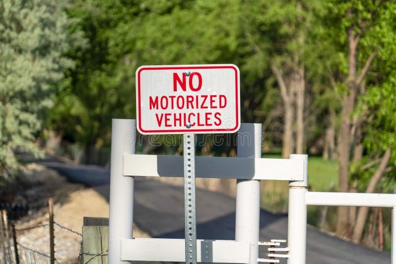 Sluit omhoog mening van een neen Gemotoriseerd Voertuigteken tegen een weg met een witte poort stock afbeeldingen