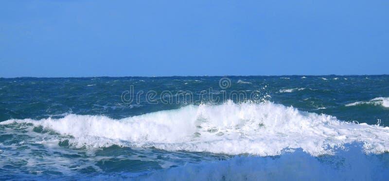 Sluit omhoog mening van een oceaangolf met wit schuim stock afbeelding