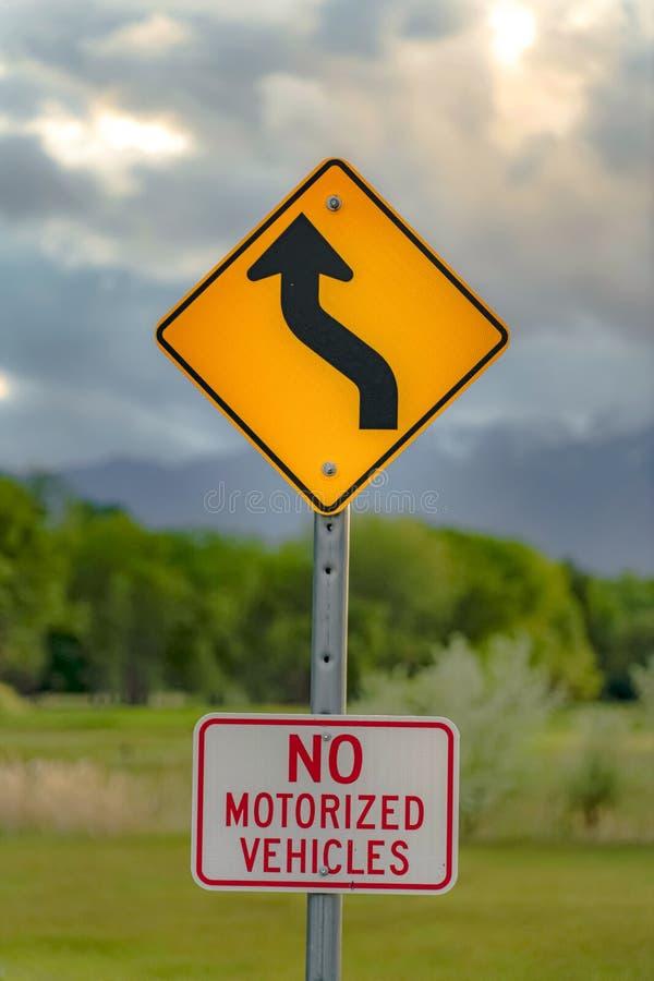 Sluit omhoog mening van een Windende Weg vooruit ondertekenen en Geen Gemotoriseerd Voertuigenteken stock foto's