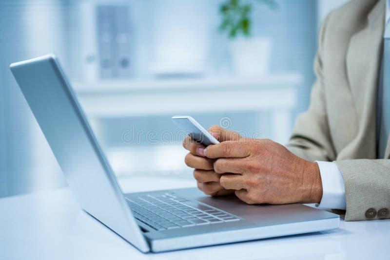 sluit omhoog mening van een zakenman gebruikend zijn telefoon stock foto
