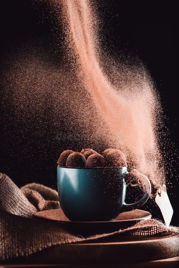sluit omhoog mening van geraspte chocolade die op truffels in kop van koffie op jute en scherpe raad vallen stock foto's