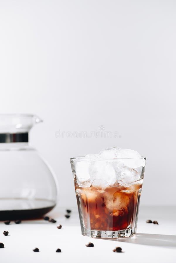 sluit omhoog mening van glas koude gebrouwen koffie, koffiezetapparaat en geroosterde koffiebonen op grijze achtergrond royalty-vrije stock afbeeldingen