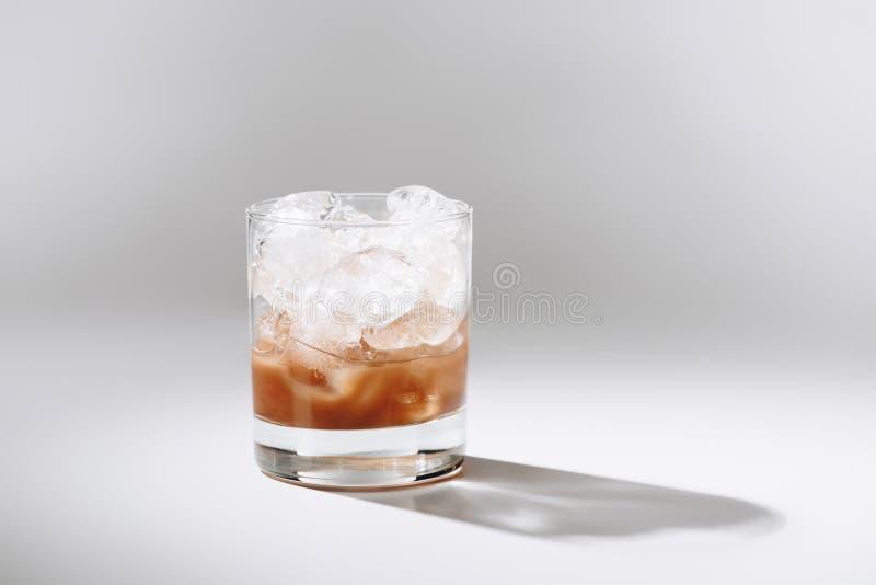 sluit omhoog mening van glas koude gebrouwen koffie met ijsblokjes op wit tafelblad stock afbeelding