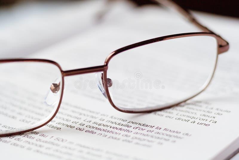 Sluit omhoog mening van glazen op het open boek stock foto's