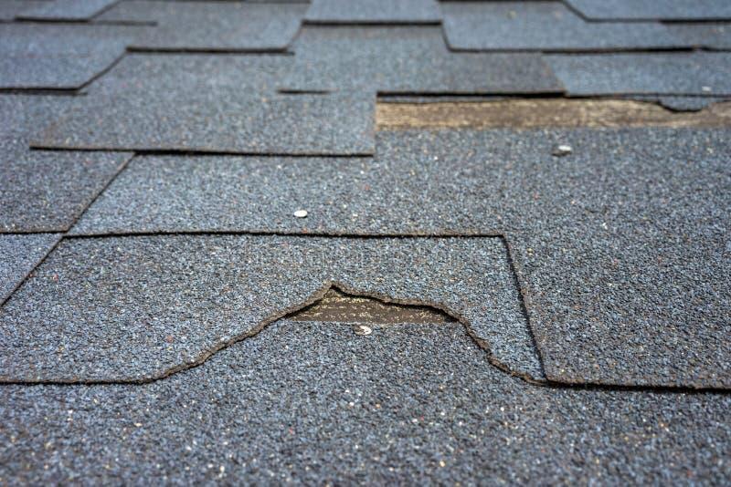 Sluit omhoog mening van het dakschade van bitumendakspanen die reparatie vergt royalty-vrije stock afbeeldingen