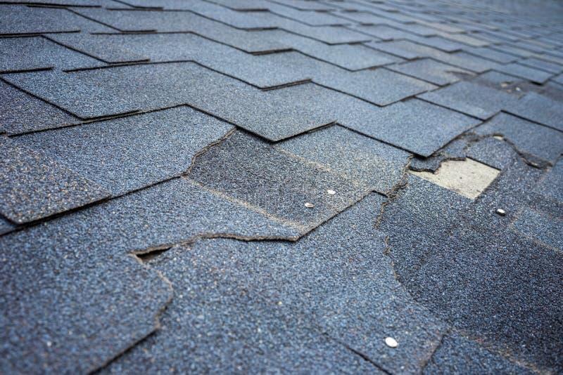 Sluit omhoog mening van het dakschade van bitumendakspanen die reparatie vergt royalty-vrije stock foto's