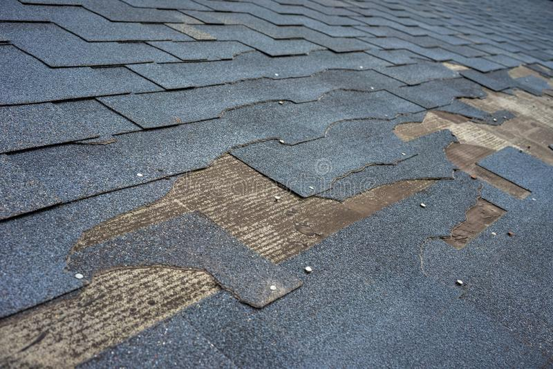 Sluit omhoog mening van het dakschade van bitumendakspanen die reparatie vergt stock afbeeldingen