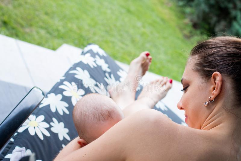 Sluit omhoog mening van het de borst geven van moeder, jonge blootvoetse mammazitting op dek en het voeden van weinig baby stock foto's