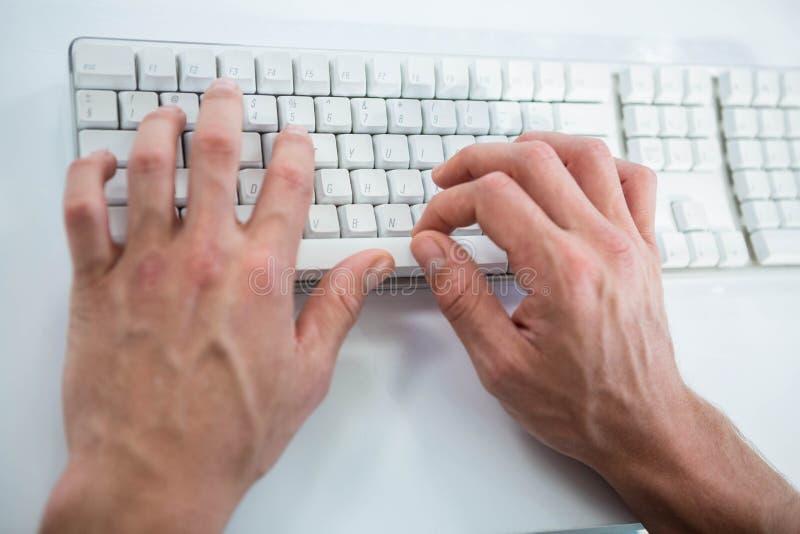 Sluit omhoog mening van het mannelijke hand typen op toetsenbord stock foto's