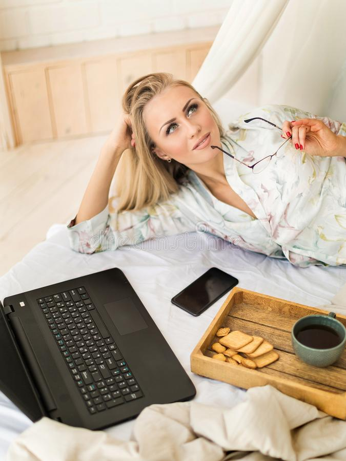 Sluit omhoog mening van het werk van de dreamig freelance vrouw thuis Slaapkamer, laptop en telefoon Ontbijt stock afbeelding