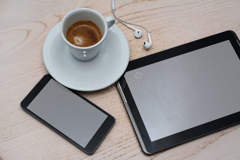 Sluit omhoog mening van koffie, oortelefoons, tablet en cellphone op houten achtergrond royalty-vrije stock foto's