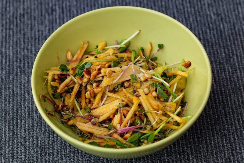 Sluit omhoog mening van kom met gezonde salade van populaire spruiten, avocado, pijnboomzaden, raap Gezond voedselconcept royalty-vrije stock fotografie