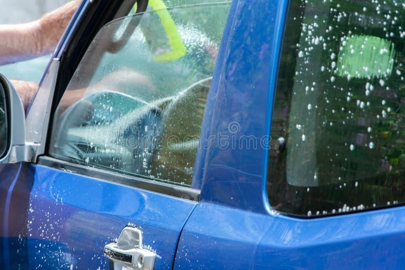 Sluit omhoog mening van mensenhanden die auto wassen royalty-vrije stock foto