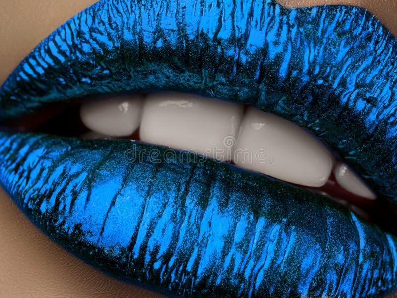 Sluit omhoog mening van mooie vrouwenlippen met blauwe metaal lipstic stock fotografie