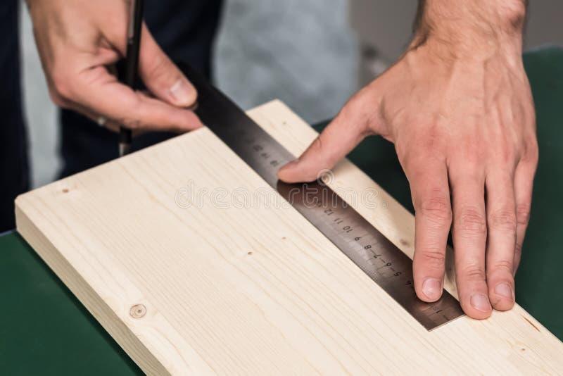 Sluit omhoog mening van persoon-mens handholding die heersershulpmiddel meet een stuk van hout voor knipsel stock afbeeldingen