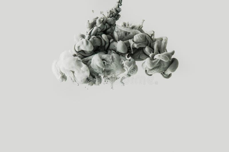 Sluit omhoog mening van rook of het mengen van lichtgrijze en zwarte die vervenplonsen in water op grijs worden geïsoleerd royalty-vrije stock afbeeldingen