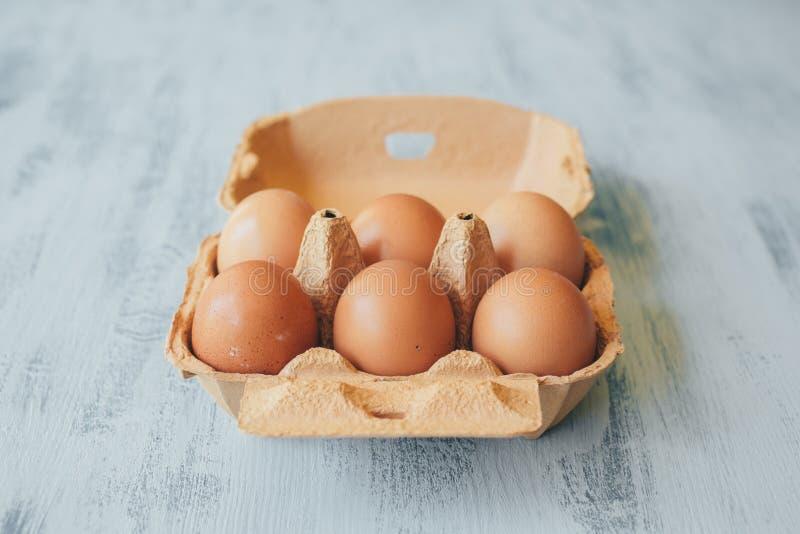 Sluit omhoog mening van ruwe kippeneieren in eivakje op witte houten lijst stock foto