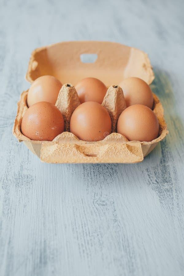 Sluit omhoog mening van ruwe kippeneieren in eivakje op witte houten lijst stock fotografie