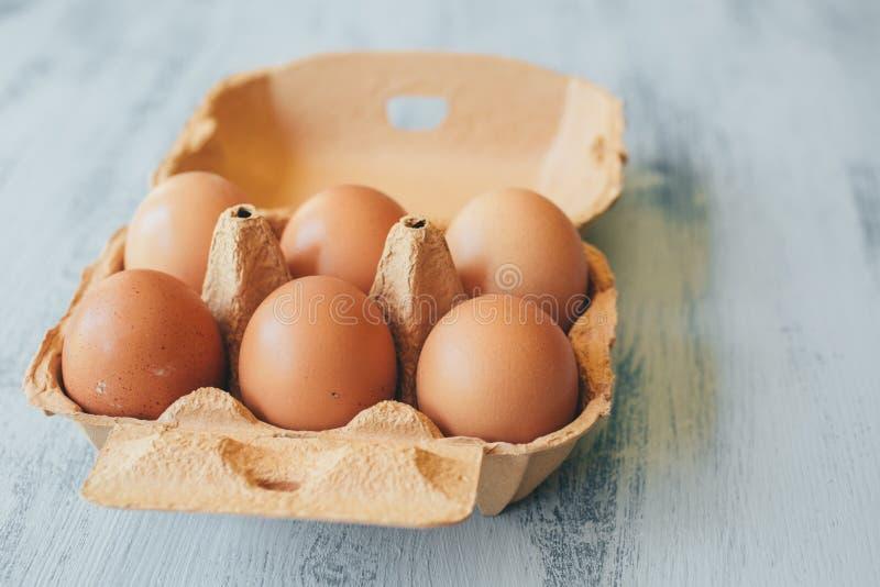 Sluit omhoog mening van ruwe kippeneieren in eivakje op witte houten lijst royalty-vrije stock afbeelding