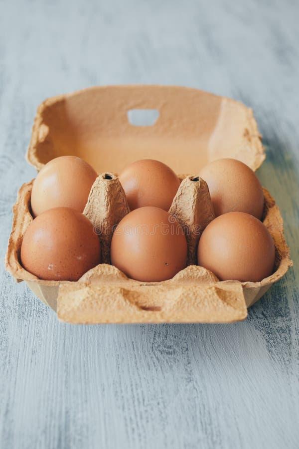 Sluit omhoog mening van ruwe kippeneieren in eivakje op witte houten lijst royalty-vrije stock foto's