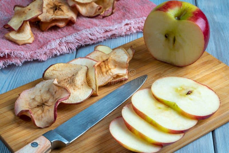 Sluit omhoog mening van smakelijke appelspaanders en rood vers appel en mes op houten achtergrond stock fotografie