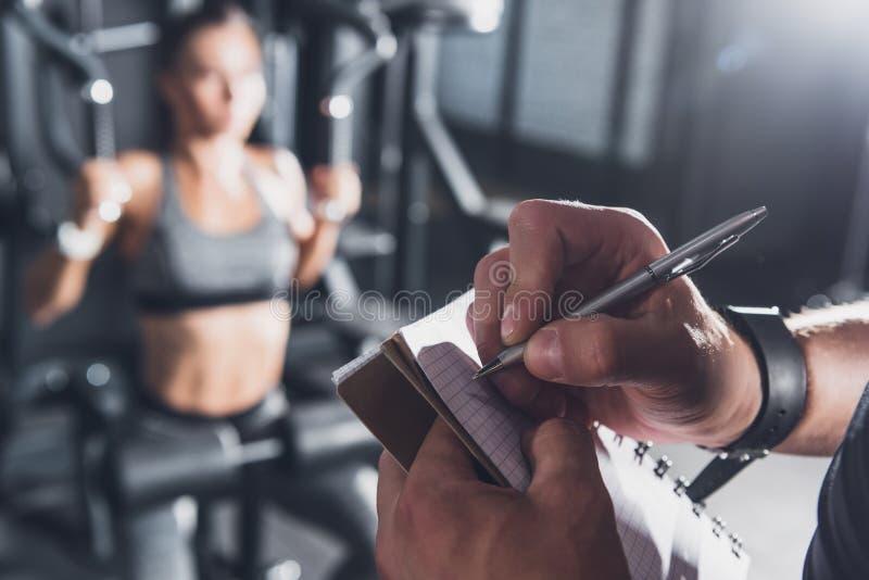 sluit omhoog mening van trainer het schrijven in notitieboekje terwijl vrouw stock foto