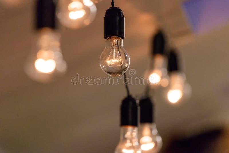 Sluit omhoog mening van uitstekende decoratieve lichte lampbol die op het plafond binnen gloeien Transparante lampen die met warm royalty-vrije stock foto