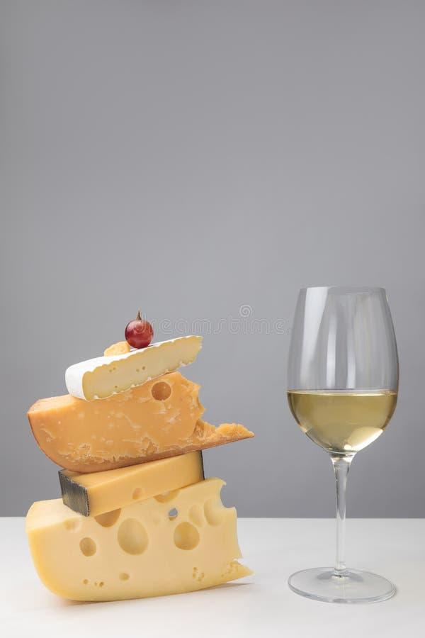 Sluit omhoog mening van witte wijnglas en druif op stapel verschillende types van kaas op grijs royalty-vrije stock foto