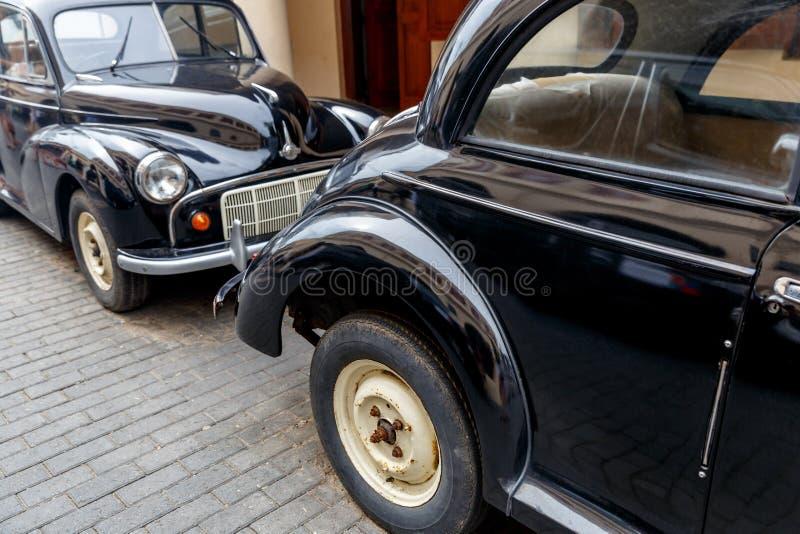sluit omhoog mening van zwarte die retro auto's op straat worden geparkeerd stock foto's
