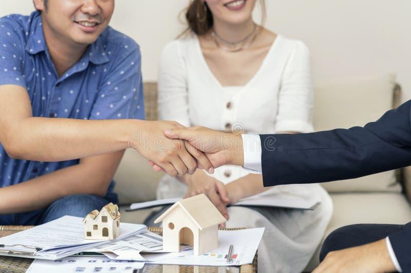 Sluit omhoog, Mens het schudden vertegenwoordigen de handen verkoop, Aziatisch paar die financiële adviseur voor huis, onroerende stock afbeelding
