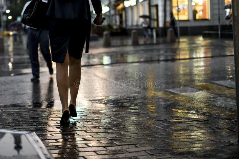 Sluit omhoog mensen die in de stadsstraat tijdens zware regen lopen royalty-vrije stock afbeelding