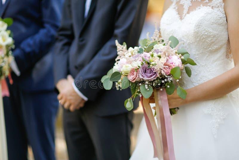 Sluit omhoog met handen van bruidegom en bruidholdingsboeket van bloem stock afbeelding