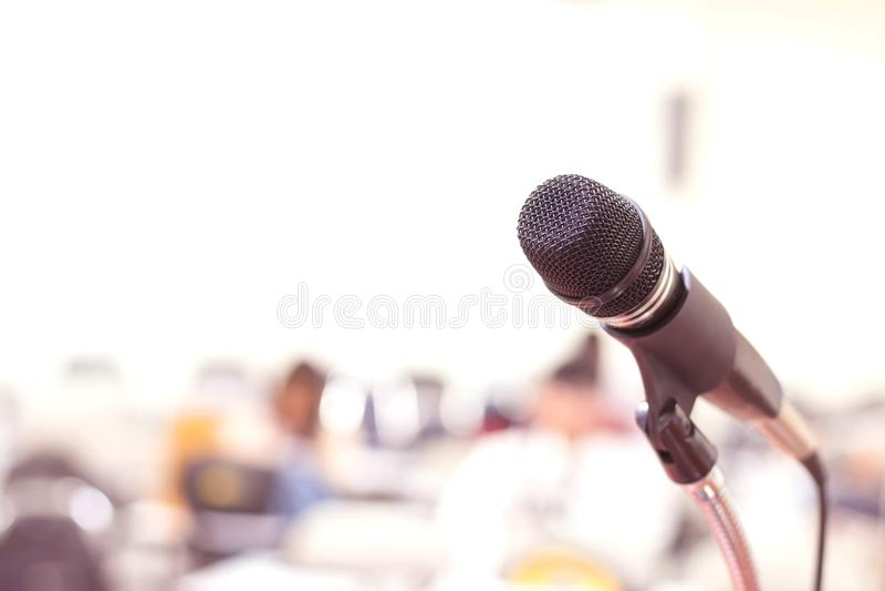 Sluit omhoog microfoon in conferentie over de gebeurtenisachtergrond van de seminarieruimte stock fotografie