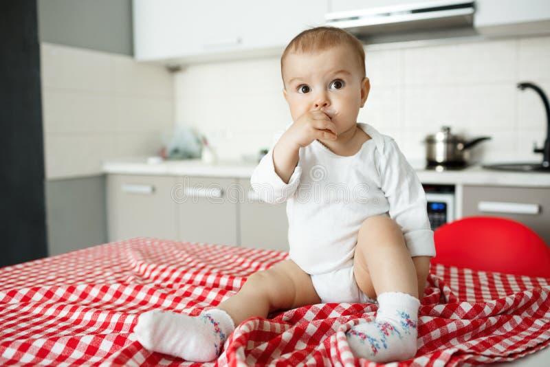 Sluit omhoog mooi portret van weinig jong geitje met grote bruine ogen zittend op keukenlijst met rood tafelkleed terwijl moeder stock fotografie