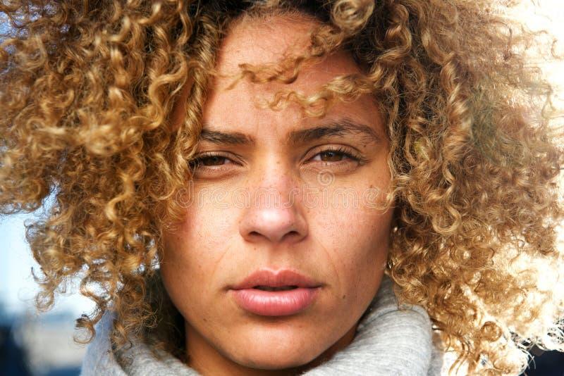 Sluit omhoog mooie Afrikaanse Amerikaanse vrouw met het krullende haar staren royalty-vrije stock afbeelding