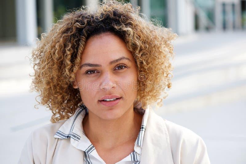 Sluit omhoog mooie Afrikaanse Amerikaanse vrouw met krullend haar en het staren royalty-vrije stock foto's