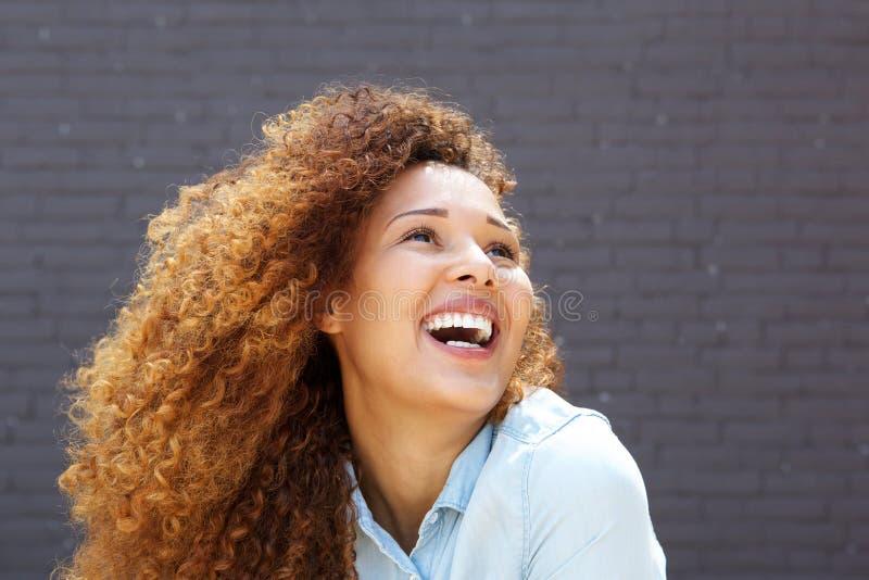 Sluit omhoog mooie jonge vrouw met krullend en haar die omhoog glimlachen eruit zien stock afbeelding