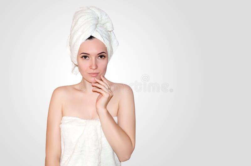Sluit omhoog Mooie Jonge Vrouw in Witte Handdoek op Hoofd na Douche op Lichte Achtergrond Zeep, handdoek en bloemensneeuwklokjes royalty-vrije stock foto's