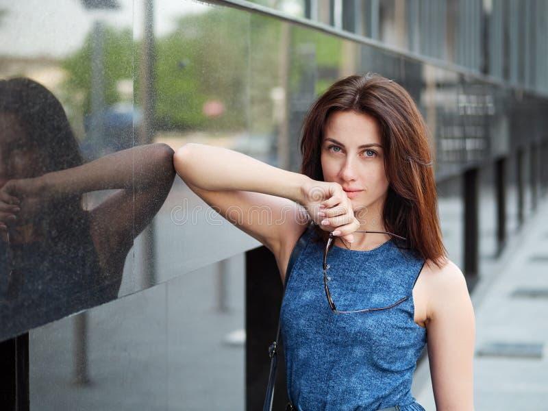 Sluit omhoog mooie volwassen roodharigevrouw in jeanskleding het stellen bij de straat stock afbeeldingen
