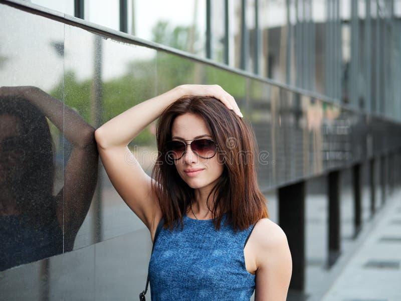 Sluit omhoog mooie volwassen roodharigevrouw in jeanskleding het stellen bij de straat stock foto's