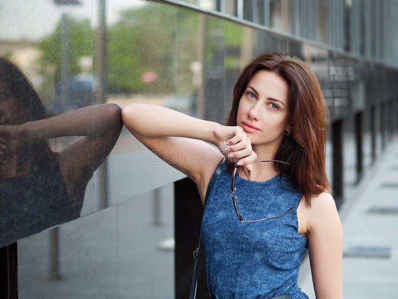 Sluit omhoog mooie volwassen roodharigevrouw in jeanskleding het stellen bij de straat royalty-vrije stock foto