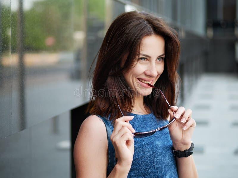 Sluit omhoog mooie volwassen roodharigevrouw in jeanskleding het stellen bij de straat royalty-vrije stock foto's