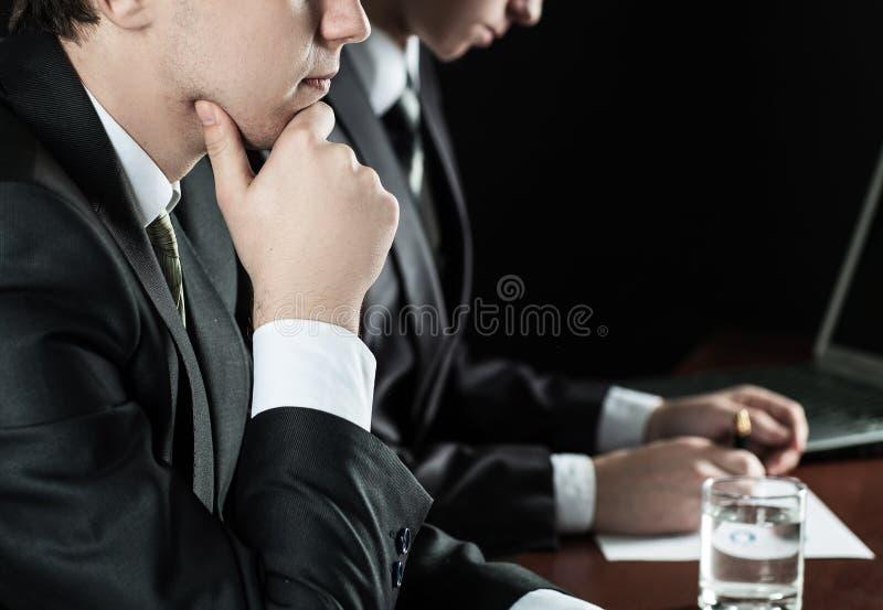 Sluit omhoog Nadenkende zakenmanzitting bij zijn bureau royalty-vrije stock foto