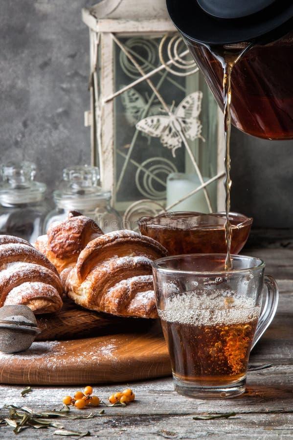 Sluit omhoog Ontbijt met vers gebakken Franse croissants De hete amberthee wordt gegoten in een glaskop in de voorgrond stock afbeeldingen