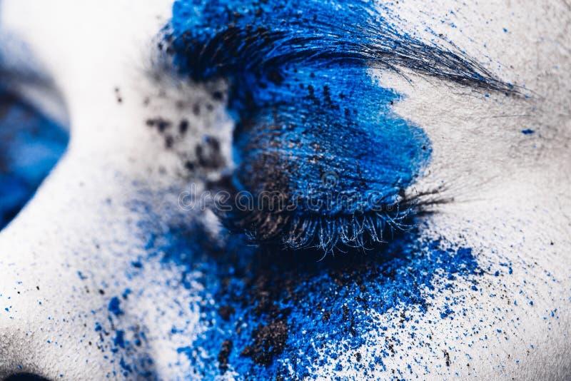Sluit omhoog oog van mannequinmeisje met kleurrijk poeder omhoog maken Schoonheidsvrouw met heldere blauwe make-up en witte huid royalty-vrije stock afbeelding