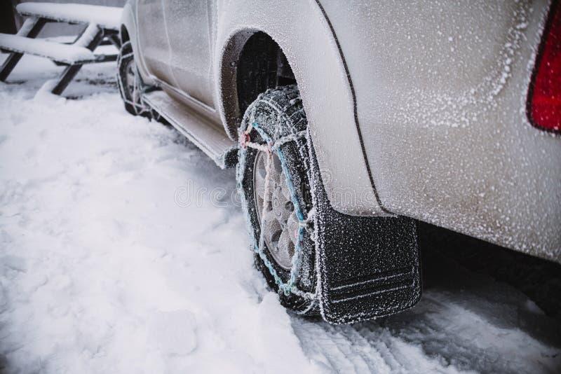 Sluit omhoog op autowiel met sneeuwkettingen De achtergrond van de winter stock fotografie