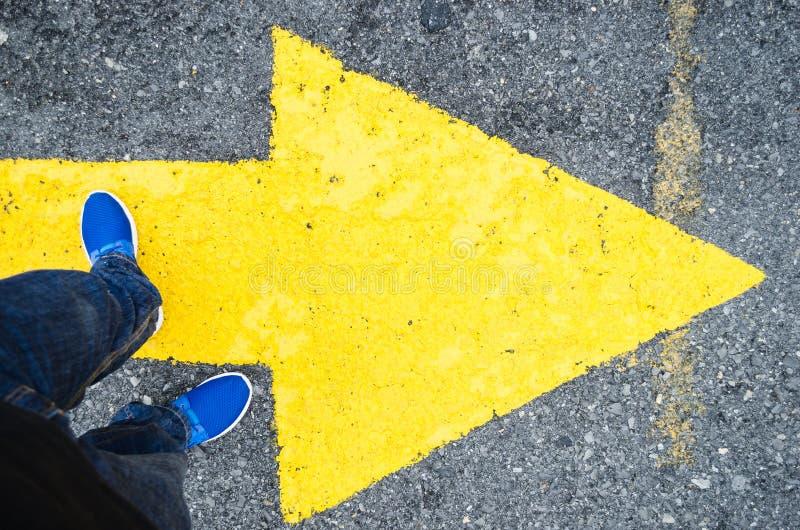 Sluit omhoog op de benen van een mens die zich op een gele pijl in de richting aan het recht bevinden, concept besluiten in het l royalty-vrije stock foto