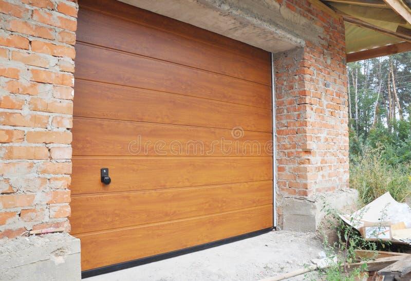 Sluit omhoog op de nieuwe geïnstalleerde raad van de garagedeur in de bouw van het bakstenen muurhuis stock foto's