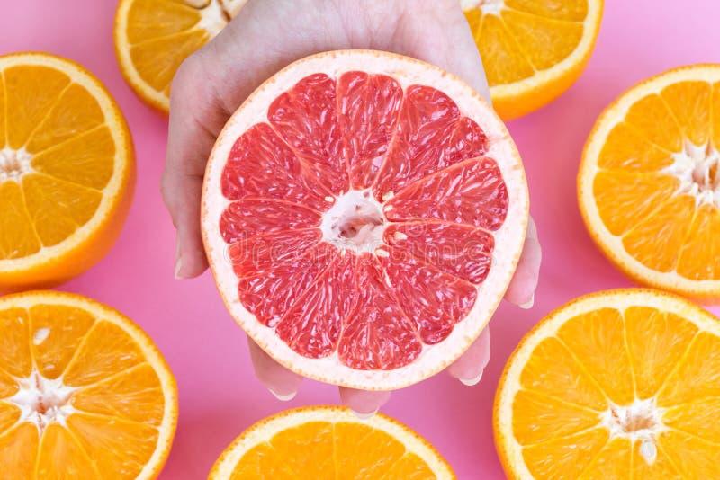Sluit omhoog op de vrouwelijke helft van de handholding van een rijpe rode grapefruit met de helften sinaasappelen royalty-vrije stock fotografie