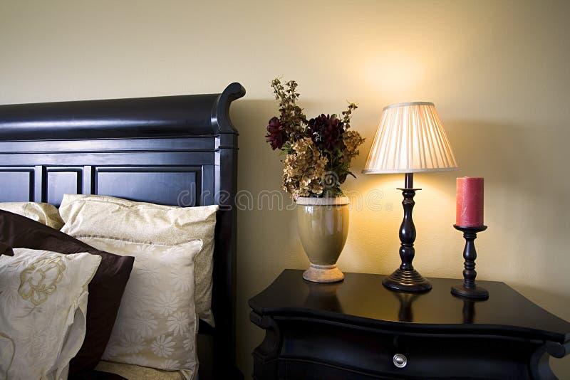 Sluit omhoog op een bed en nightstand in een slaapkamer royalty-vrije stock foto